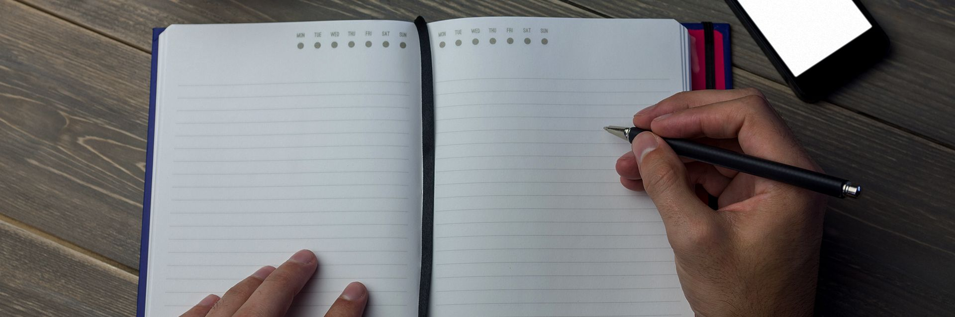 Person writing on a diary at the desk